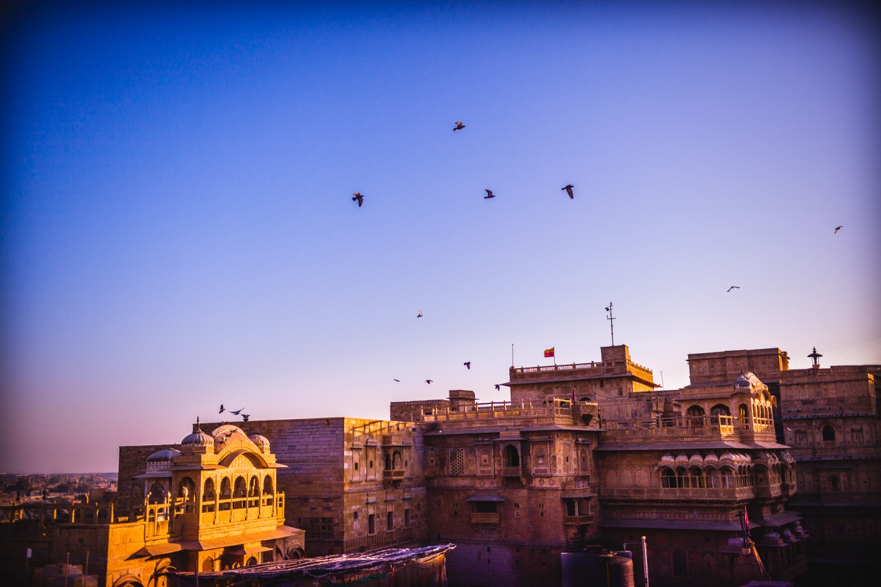 Where am I? Dance the pigeons around my head like on any public place in Paris. The sun rising over the desert is starting to reveal the golden buildings arising from the sand. Is this sun the same as before? Is there only one sun lighting all the places in the world? Certainly not. Jaisalmer, India, 2014.